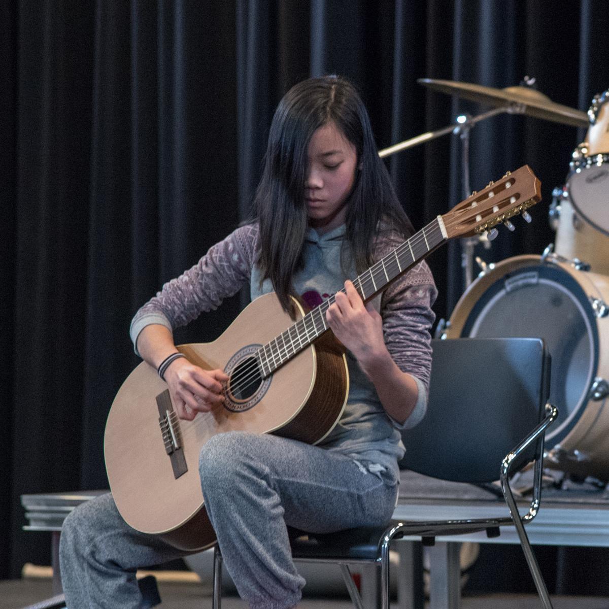 Helen plays guitar on stage, Oakville Ontario