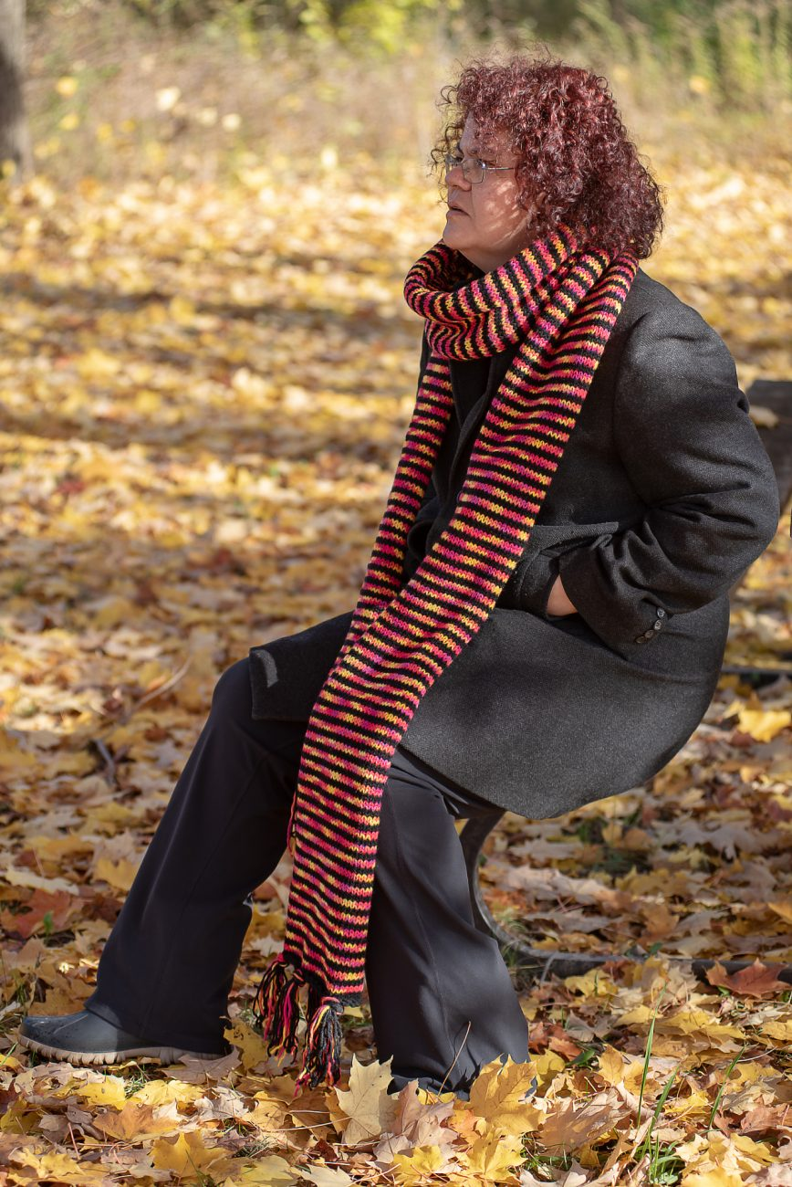 Woman sitting on a bench with a knitted scarf