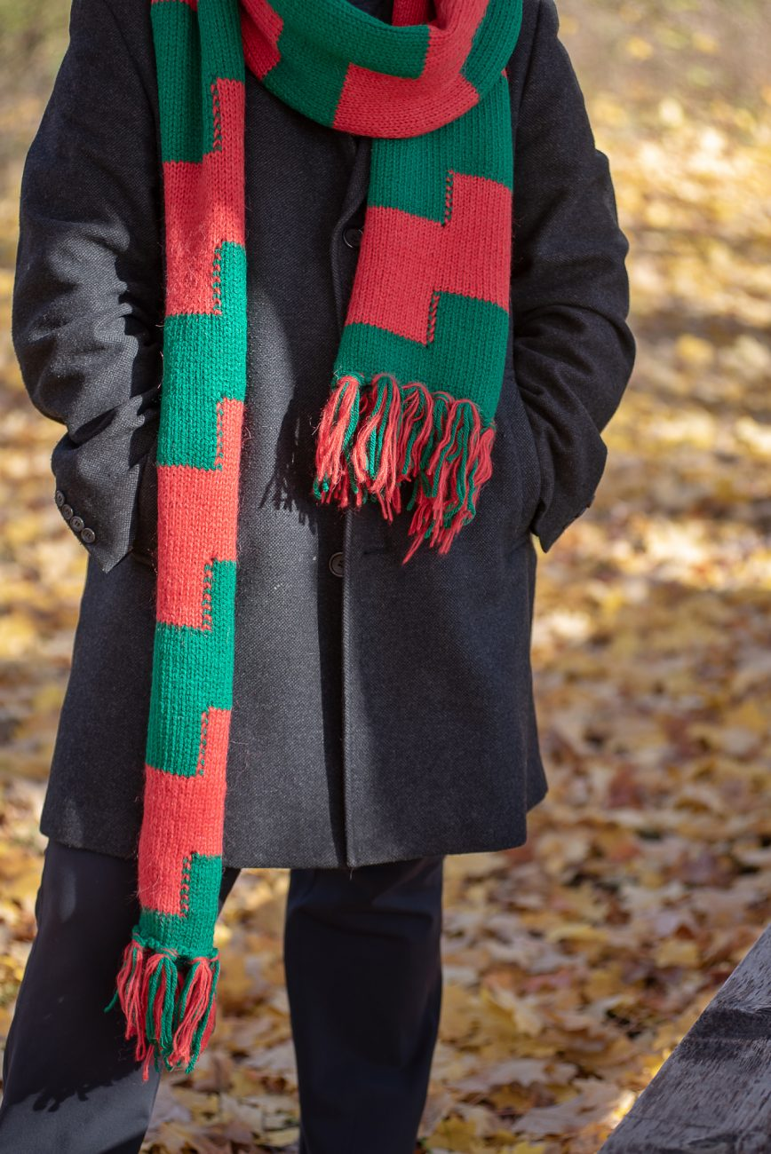 Woman standing in a coat and knitted scarf in green and red