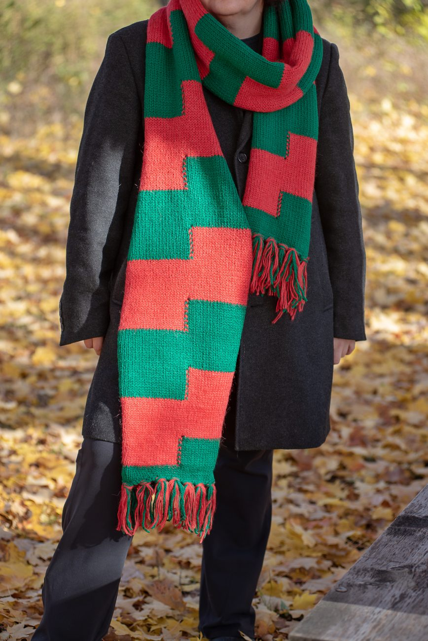 Woman standing in a coat and red and green scarf from the head down
