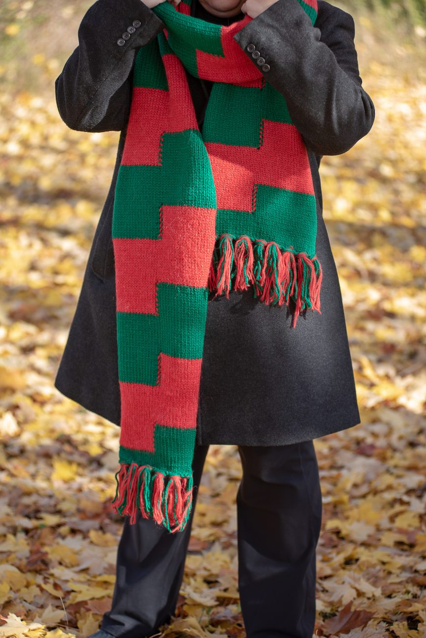 Woman with a knitted scarf in red and green from the head down