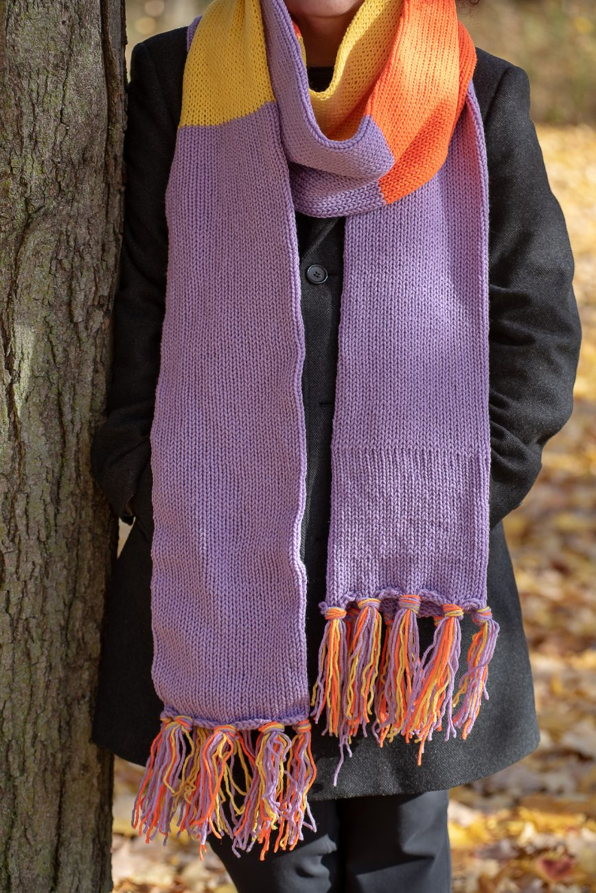 Woman standing with a long knitted scarf in purple, orange and yellow