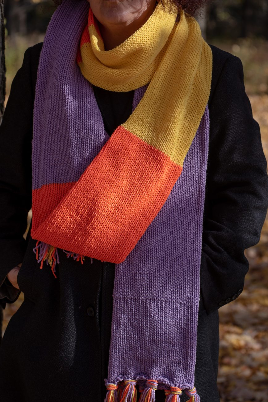 Woman wearing a purple, orange and yellow knitted scarf, close up