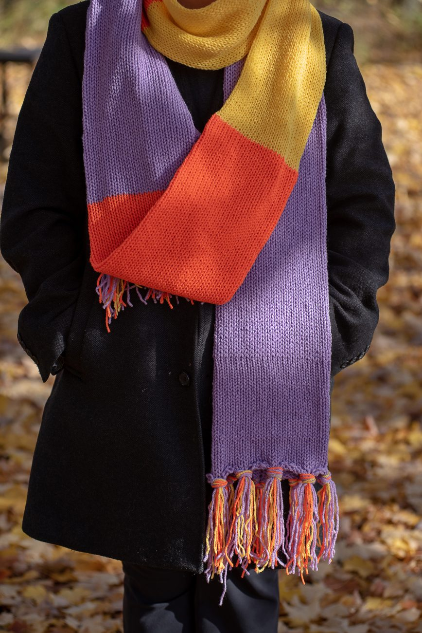 Woman wearing a purple, orange and yellow scarf, only torso