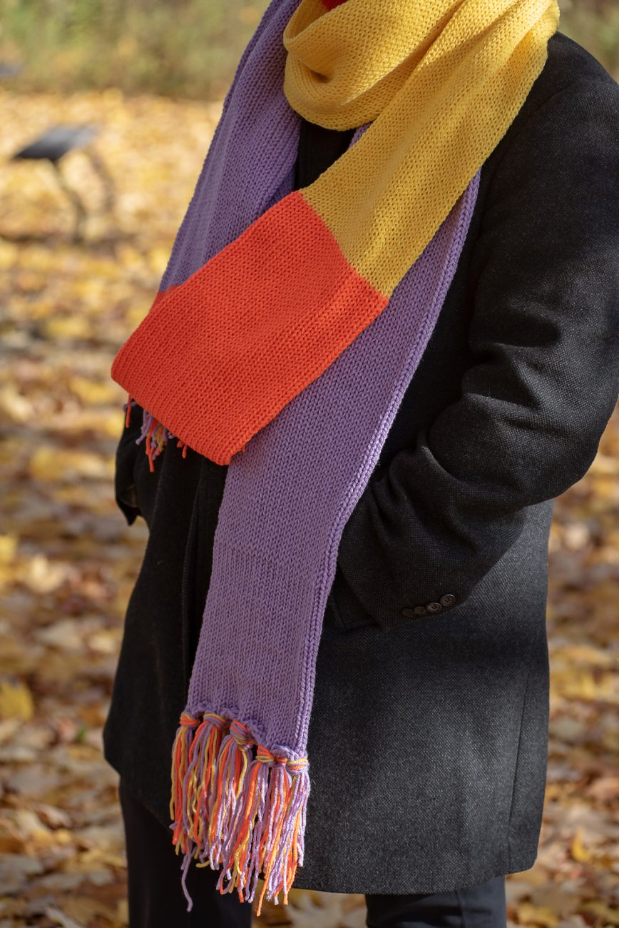 Woman wearing a purple, orange and yellow scarf