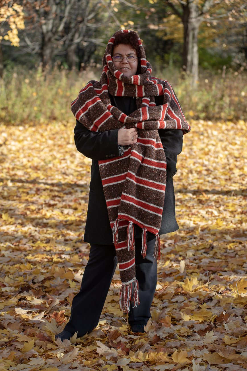 Woman wearing a huge knitted scarf in brown, red and white