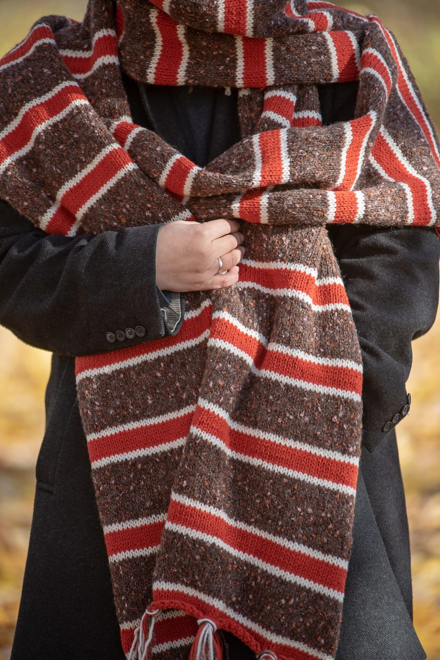 Huge knitted scarf close up, in brown, red and white on a woman's torso