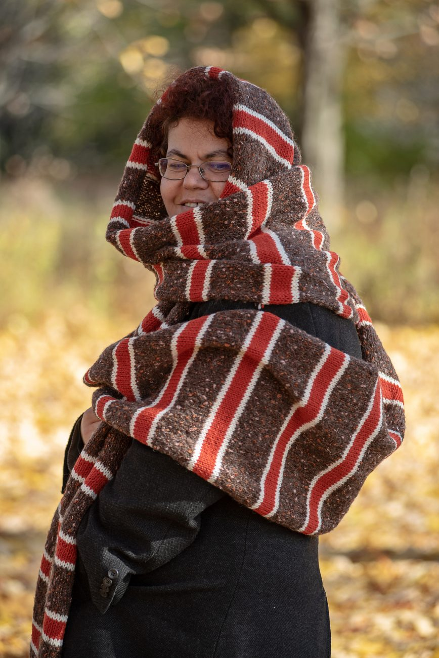 WOman covering her head with a huge knitted scarf in brown, red and white