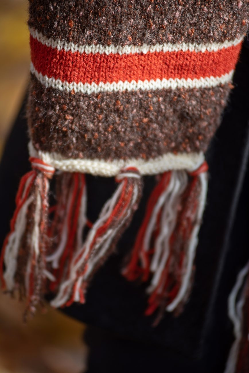 Knitted scarf in brown, red and white, detail