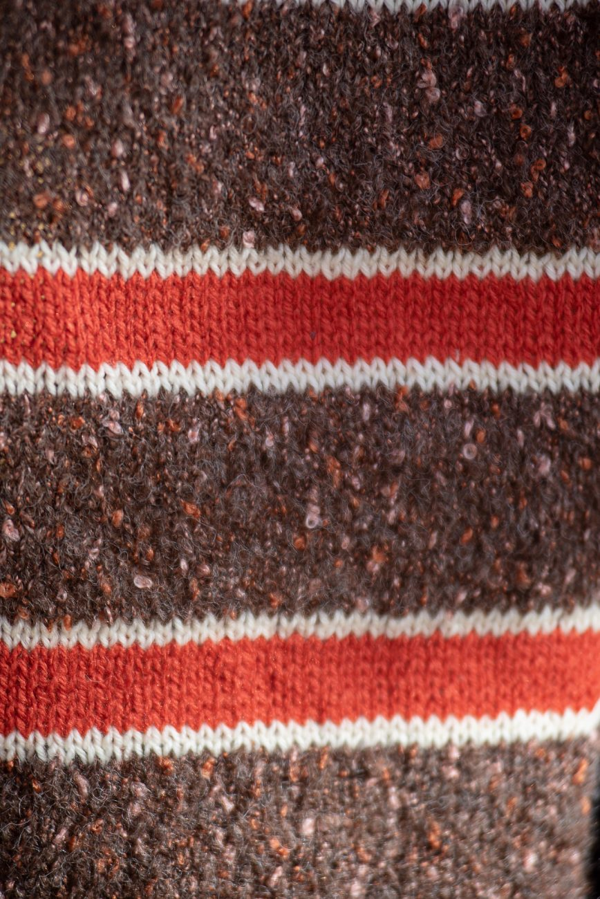 Close up detail og knitted scarf in brown, red and white