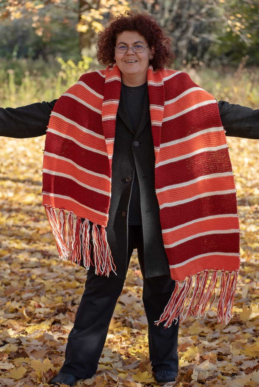 Woman standing in a huge knitted scarf in red, orange and white