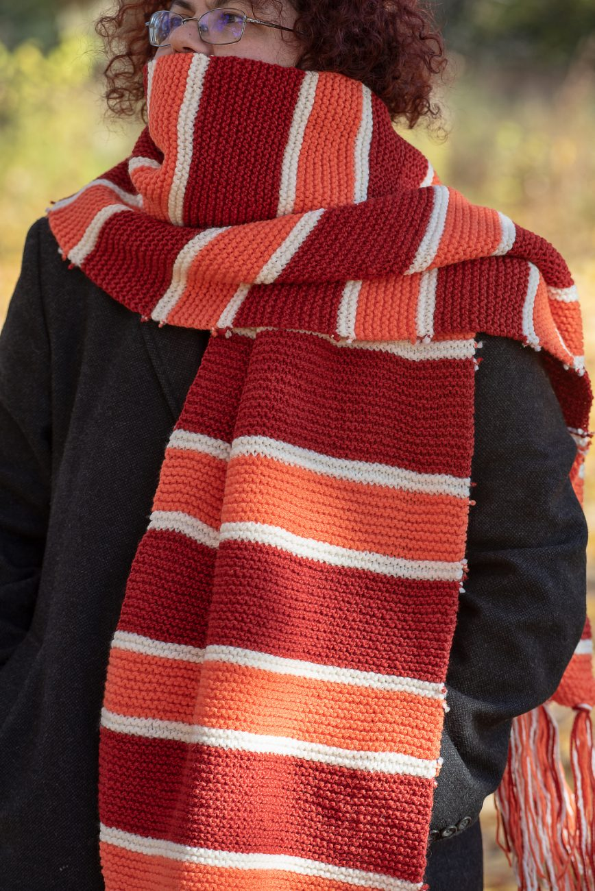 Boy in a big knitted scarf in red, orange and white