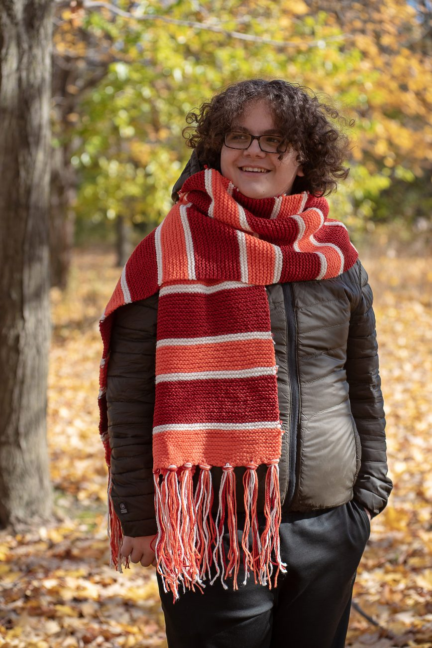 Boy standing in an orange, red and white scarf