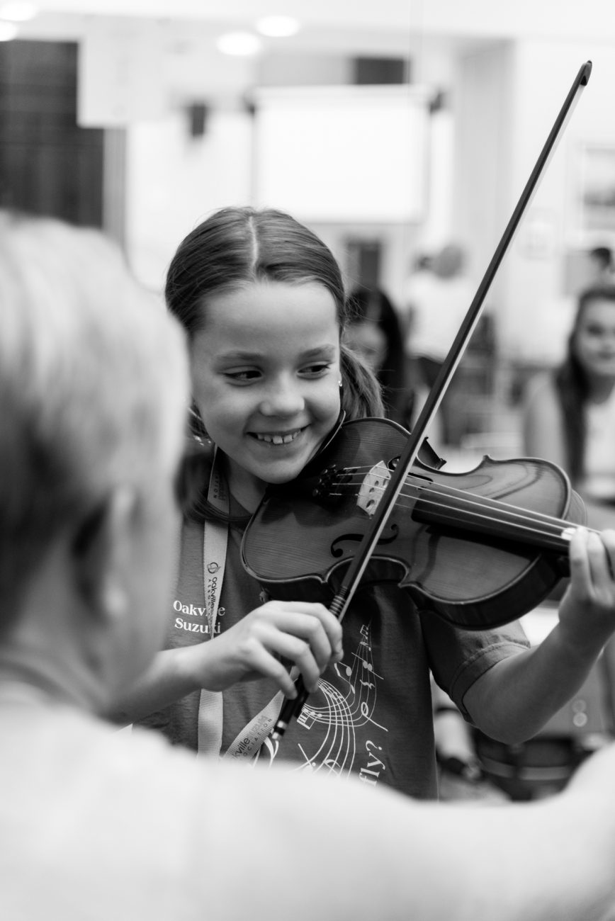 Girl playing violin and smiling